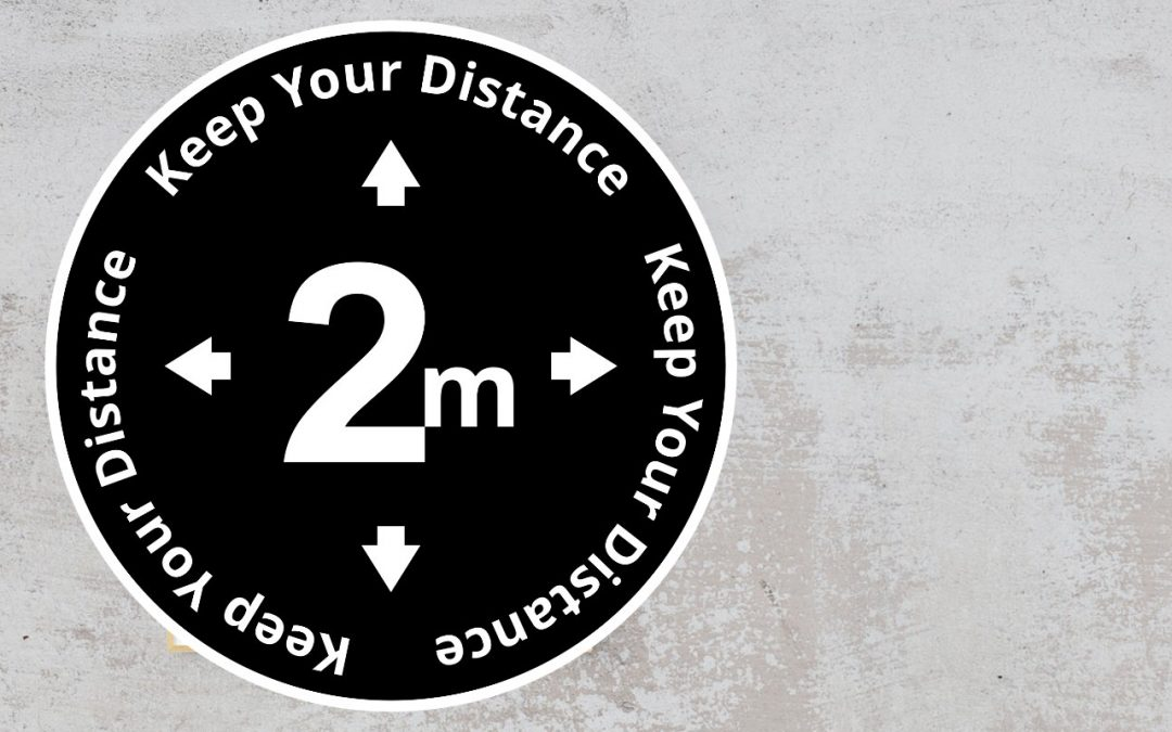 Black and white sign with the text Keep your distance 2 m