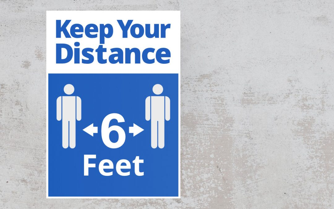 keep your distance sign on the wall